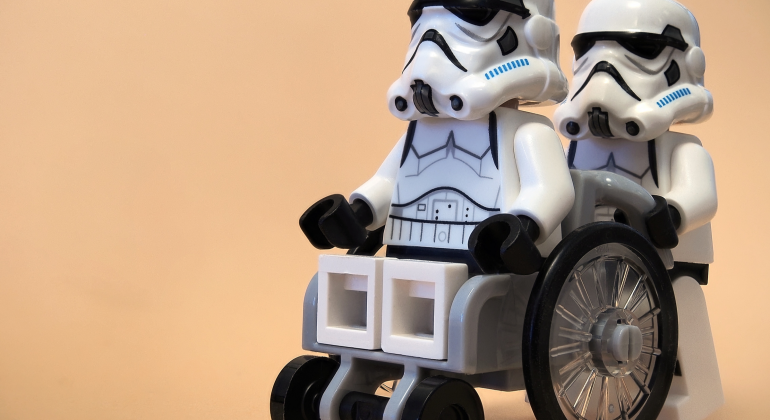 storm trooper in a wheel chair getting pushes by another storm trooper